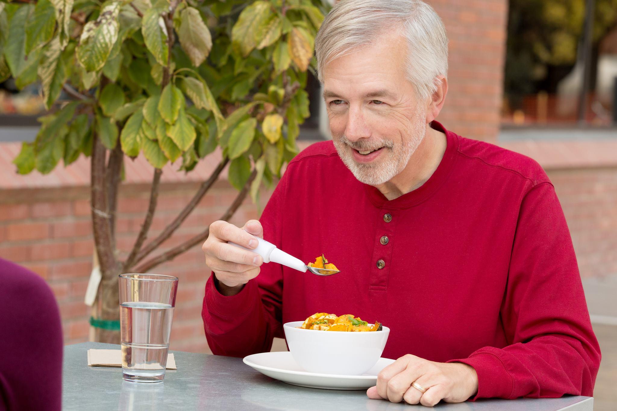 Elindeki kaşıkla önündeki kaseden çorba içmeye çalışan yaşlı bir engelli