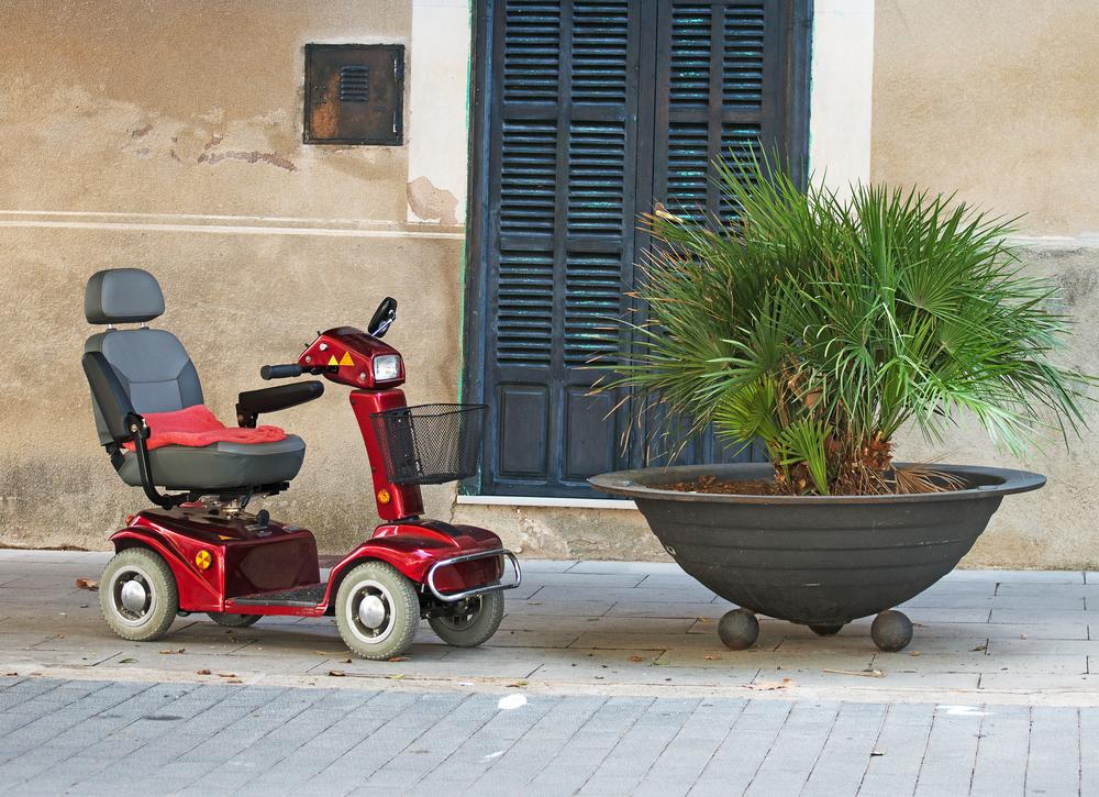 Bir binanın önünde solda boş tekerlekli sandalye ve sandalyenin sağında içinde çiçek olan büyük bir saksı görüntüsü.