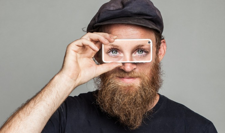 Sağ elinde bulunan büyüteci gözüne tutan sakallı bir erkek Görüntüsü