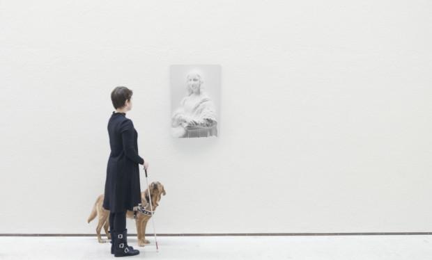 Duvarda Üç Boyutlu Bir Görüntü Var ve O Görüntünün Önünde Yanında Bir Rehper Köpeğiyle Elinde Beyaz Bastonunu Tutan Görme Engelli Bir Kadın Bulunuyor.